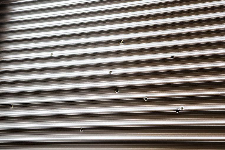 Kogelgaten in een rolluik in de Rupelstraat. Beeld Thomas Legrève
