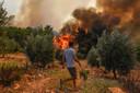 Een man loopt vandaag in de richting van bosbranden in het dorp Kacarlar in de buurt van de Turkse kustplaats Manavgat.