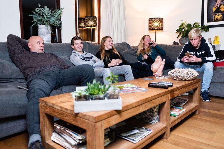 Fleur Harshagen (midden) thuis bij haar moeder in Venlo, met haar stiefvader, broer en stiefbroer met z'n allen op de bank kijkend naar voetbal. Beeld Katja Poelwijk