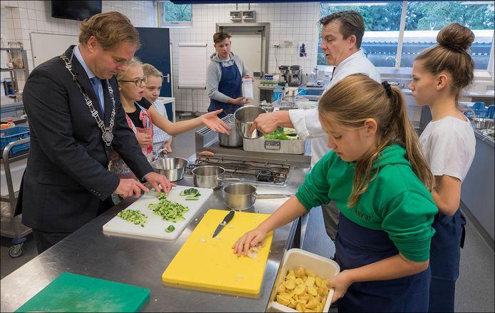 Burgemeester Antoine Walraven helpt kinderen op roc de Leijgraaf in Cuijk met koken, ter voorbereiding op een nieuwe editie van de Keukenbazen Battle, enkele jaren geleden.
