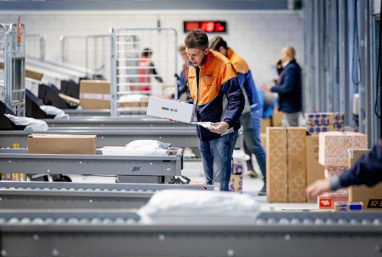 Medewerkers sorteren pakketten in een opslagcentrum van PostNL in Tilburg. Beeld ANP