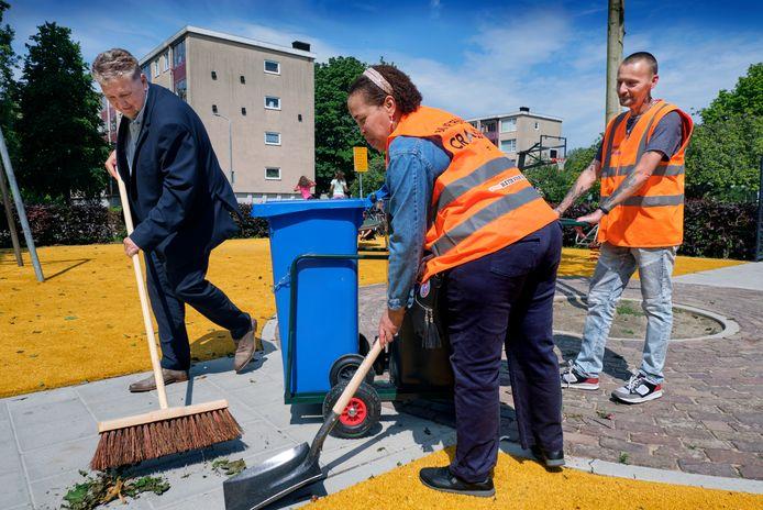 Wethouder Marco Stam (links) helpt een handje mee met schoonmaken.