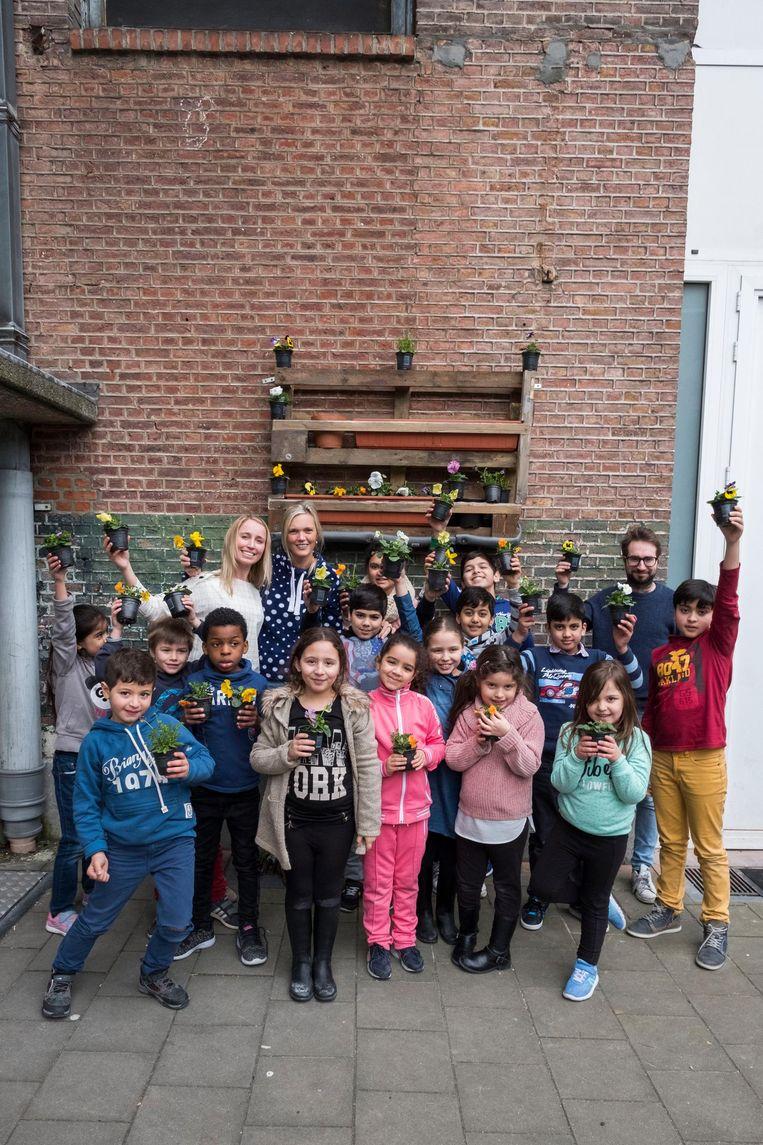 Op de foto rechts poseren leerlingen van De Zonnebloem met viooltjes op de speelplaats.