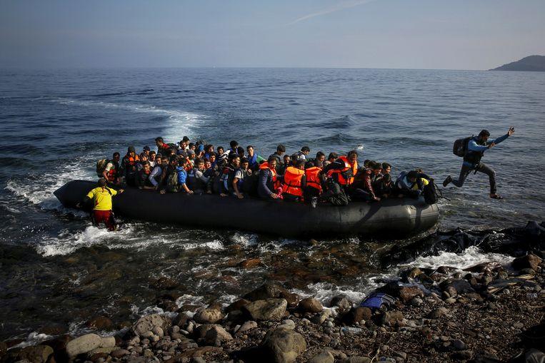 Een vluchteling springt aan land bij het Griekse eiland Lesbos. Beeld REUTERS