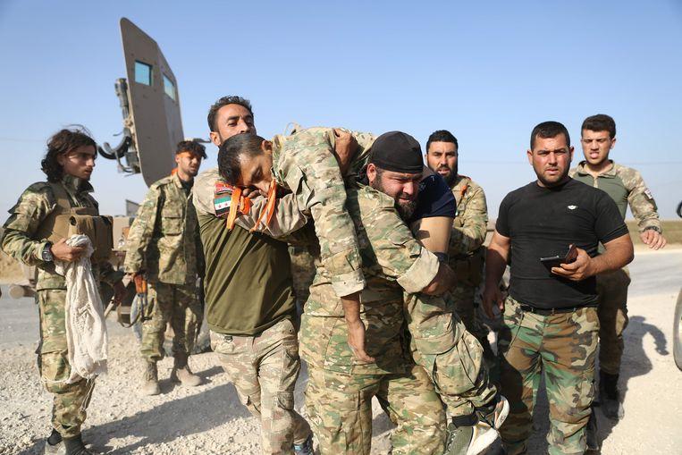 Arabische huurlingen, die samen met de Turken vechten tegen de Koerden, evacueren een gewonde soldaat nabij Ras al-Ain.  Beeld AFP