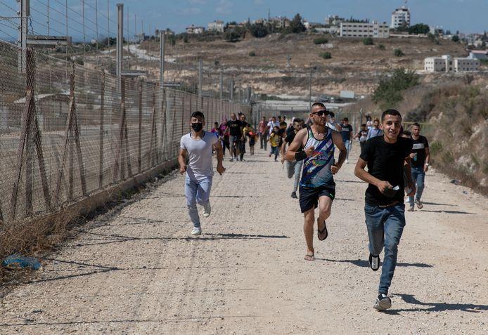 Palestijnen op de noordwestelijke Jordaanoever profiteren van een gat in een Israëlisch hek voor een dagje op het strand.