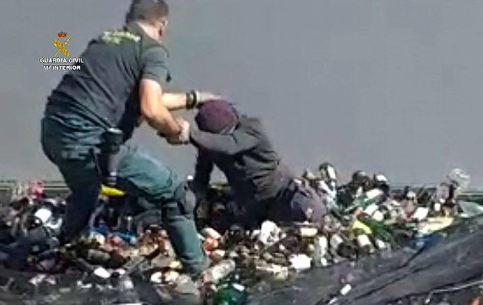 Een agent van de Guardia Civil helpt een verstekeling uit een container met glasscherven.