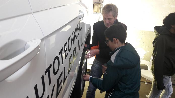 Docent Productie Installatie en Energie, Frans Oonk van het Erasmus, leert Yaser (12) hoe je een band moet verwisselen.