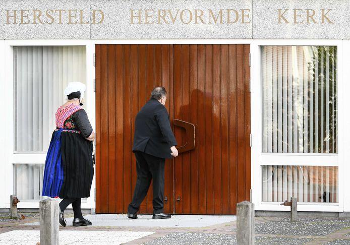 Kerkgangers komen aan bij de Hersteld Hervormde Kerk in het diepgelovige dorp Staphorst