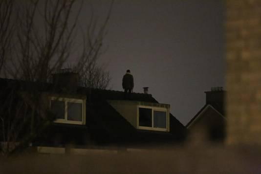 Een man met een bijl op het dak in Oudeschanspad Arnhem.