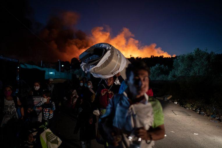 Migranten ontvluchten kamp Moria op Lesbos in september 2020 na een grote brand. Beeld AP