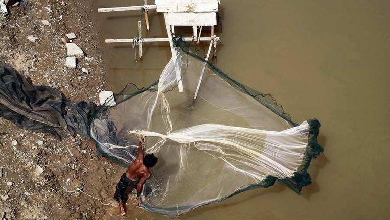 Een visser gooit zijn net uit in de Mekong rivier. Beeld reuters