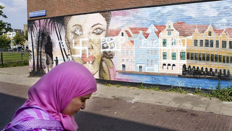 Een vrouw loopt langs een muurschildering in de Schilderswijk Beeld anp