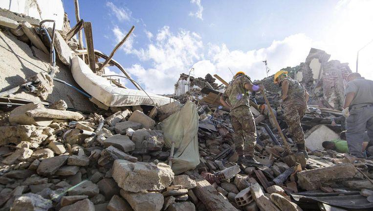 Soldaten zoeken na de aardbeving in het puin naar vermisten, in het Centraal-Italiaanse dorpje Amatrice. Beeld epa