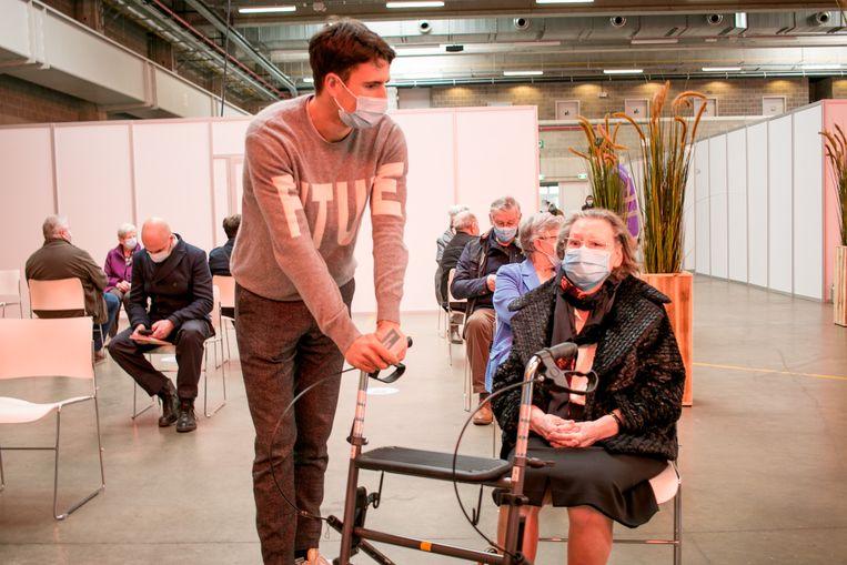 Voorzitter Conner Rousseau met zijn oma in een vaccinatiecentrum in Sint-Niklaas. De Vooruit-voorzitter pleit voor massaal testen. Beeld JVS