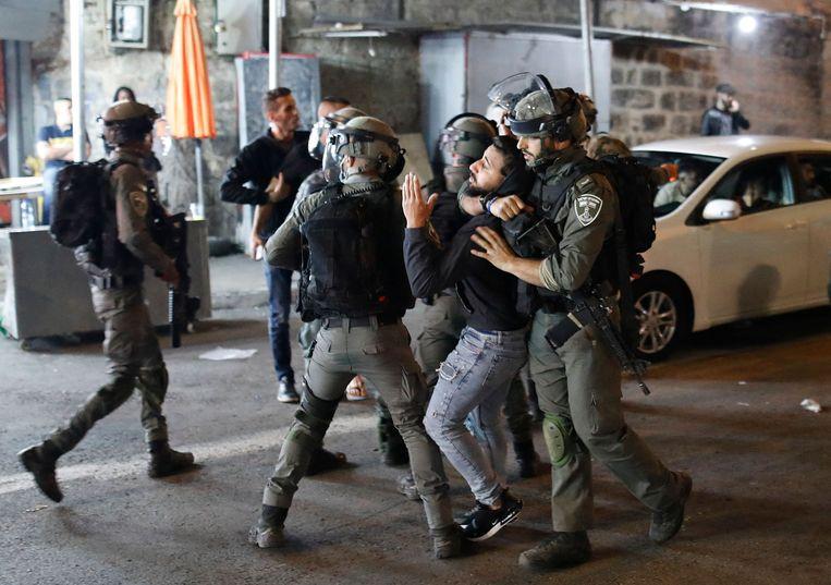 Israëlische veiligheidsdiensten arresteren een Palestijnse demonstrant. (23/04/2021) Beeld AFP