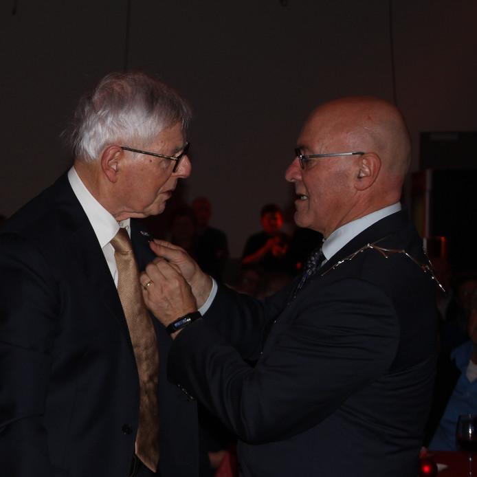 Jubilaris Harry Donjacour krijgt het KNMO-speldje opgestoken door burgemeester Kees van Rooij.