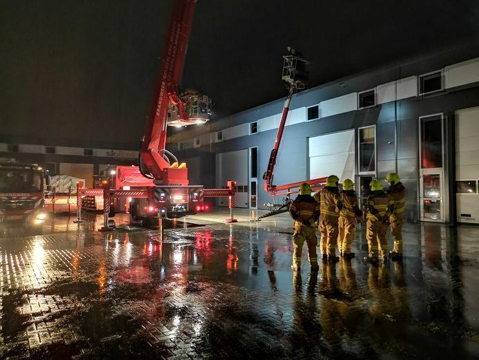 De brandweer heeft twee mannen uit een hoogwerker gered bij een bedrijfspand aan de Voltastraat in Ede.