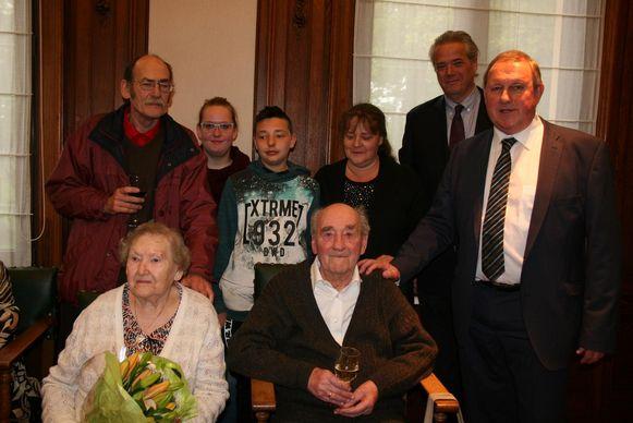 Jaak De Backer en Julia Nuyts (vooraan) met hun familie en burgemeester Dirk Van Mechelen(rechts).