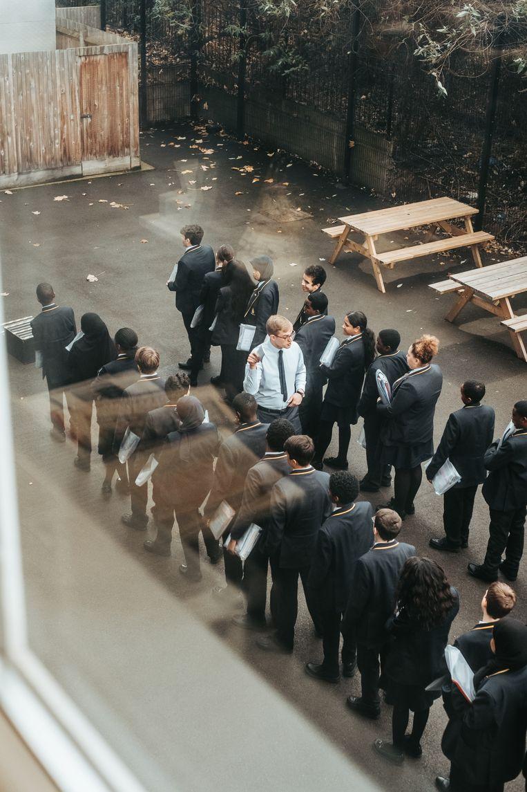 Leerlingen staan in de rij van de kleine speelplaats.  Beeld Illias Teirlinck