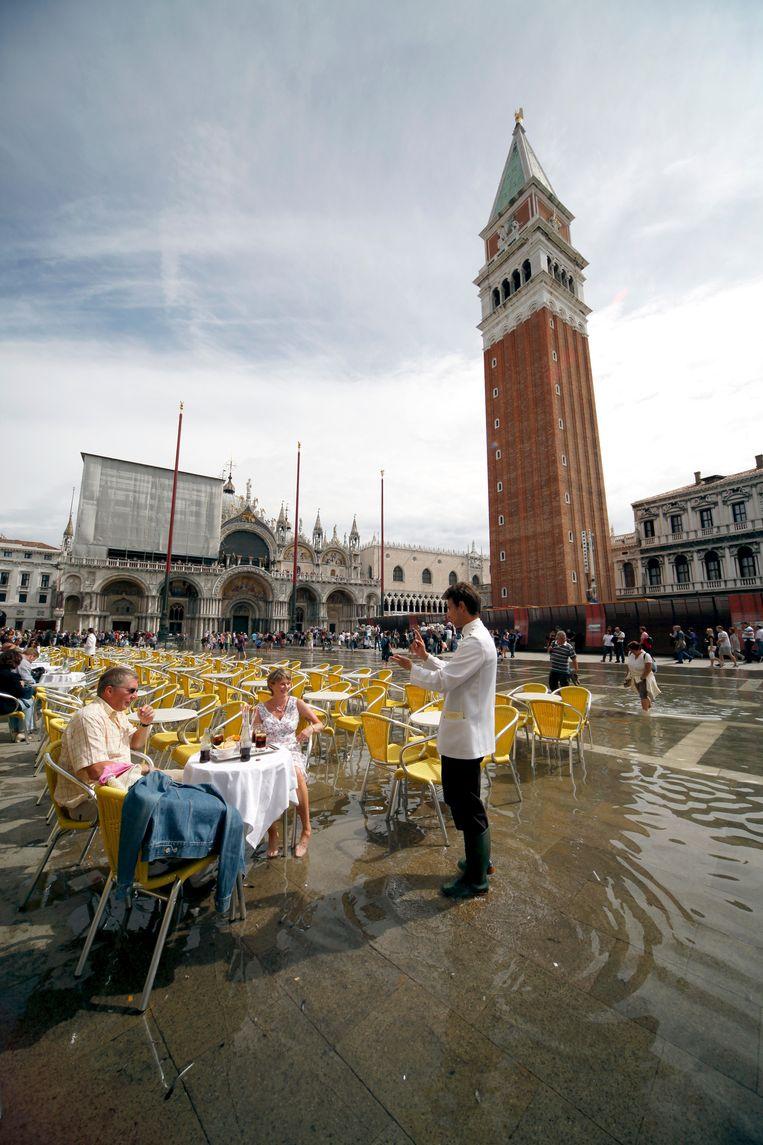 Twee eenzame toeristen genieten op het overstroomde San Marcoplein in Venetië. Beeld Allstar