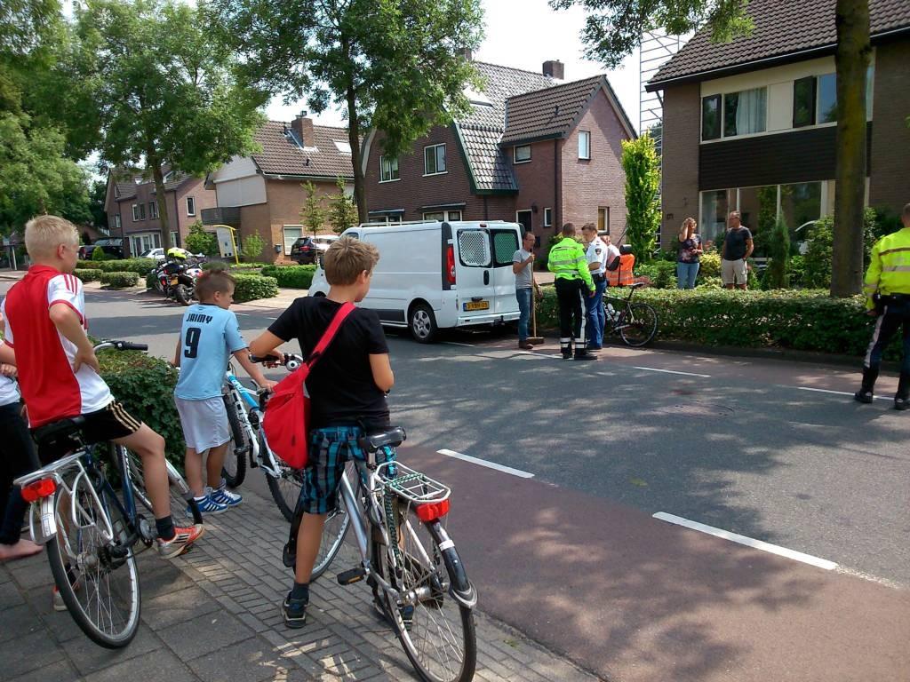 Jongens kijken naar de plek waar net een wielrenner op een busje is gebotst. foto Gert Budding