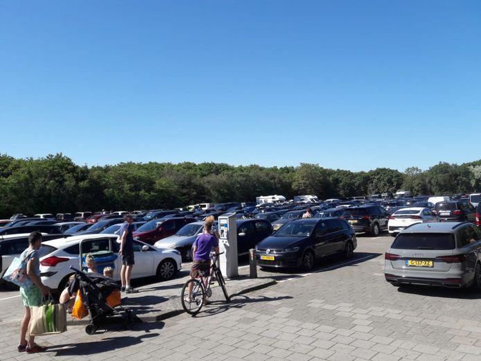 Het parkeerterrein bij het strand in Oostkapelle stroomt vol. Er is geen plekje meer te vinden.