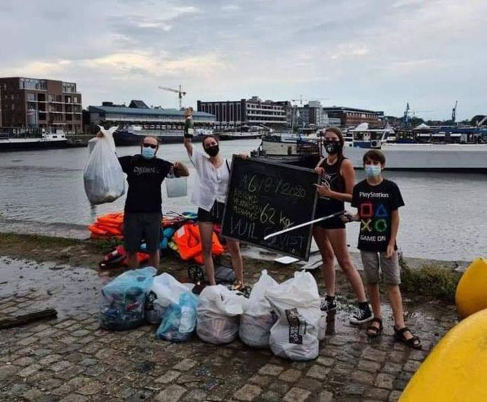 Leden van Jeugdhuis Asgaard tonen trots hun recordhoeveelheid afval die ze uit het water haalden.