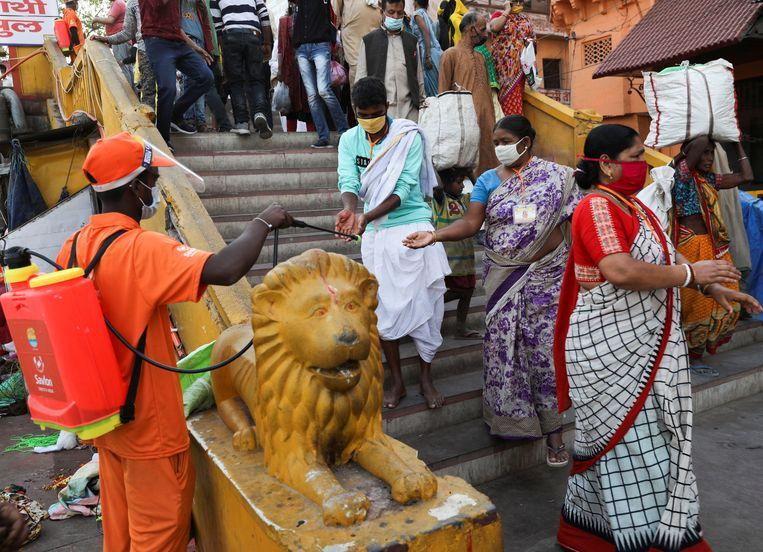 Een eerstelijnswerker spuit ontsmettingsmiddel op de handen van gelovigen aan de Ganges tijdens een religieuze ceremonie.  Beeld REUTERS