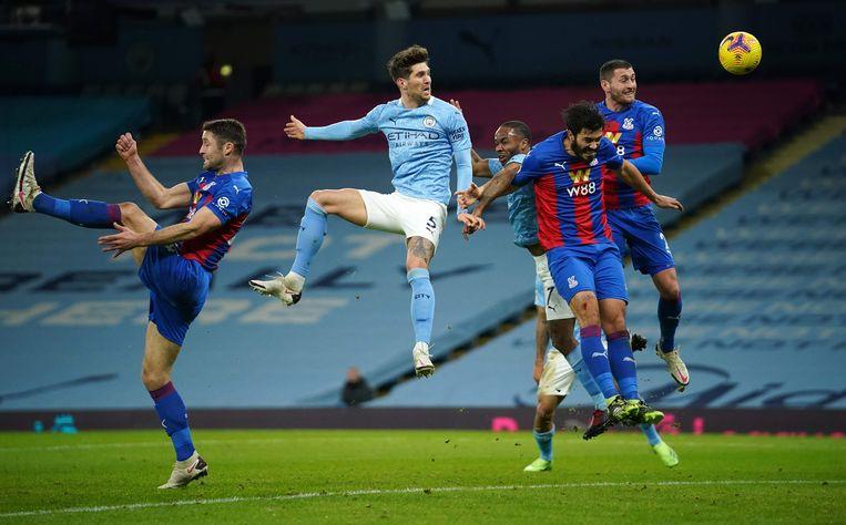 Manchester City-verdediger John Stones kopt naar het doel van Crystal Palace in het Etihad Stadium. Beeld AFP