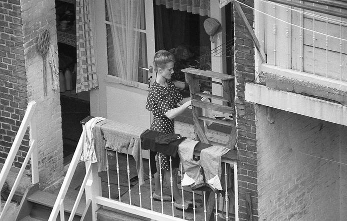 Achterzijde Cronjéstraat, 1964. Een moeder in de weer met de was.