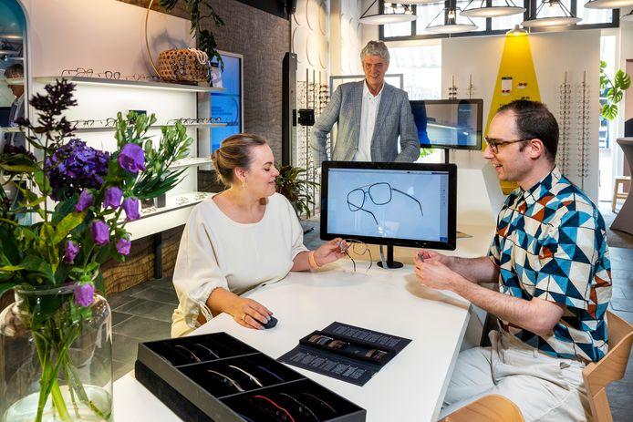 Een medewerkster van Oogzorg Thijssen laat via het scherm de modellen zien die in de winkel niet aanwezig zijn. Louis Du Pré kijkt op afstand toe. Foto: Gerard Burgers.
