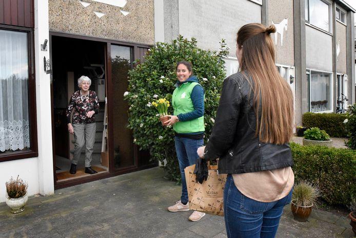 Tiny Fierens (m) krijgt een maaltijd en een bloemetje overhandigd van Lotte Ruyten van Thuishuis Woerden (groen hesje) en Lieke Voss van Broodje Midas. Foto Rianne den Balvert