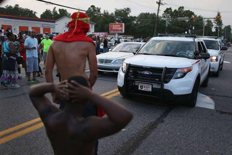 Demonstranten staan voor politieauto's in Ferguson Beeld afp