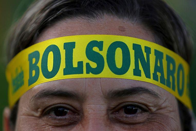 Een aanhanger van Bolsonaro draagt zijn naam op haar hoofd. Beeld AP