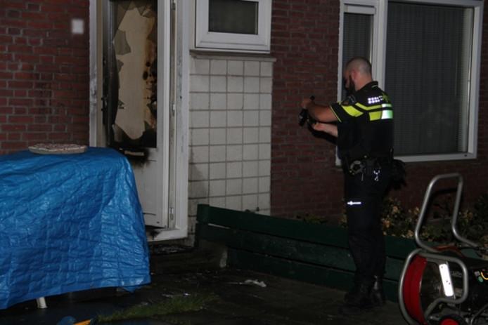 Een agent maakt foto's van de zwaar beschadigde voordeur.