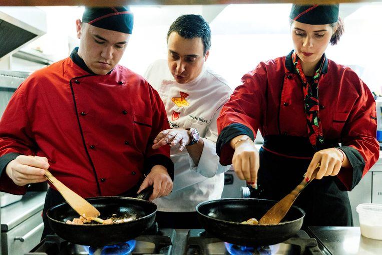 Een kok geeft twee jongeren instructies. Beeld AFP