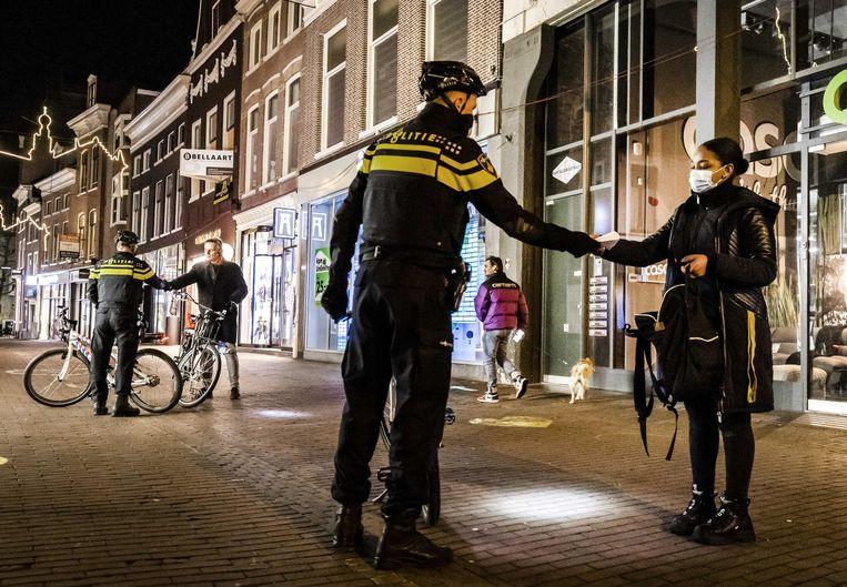 Politie vraagt voorbijgangers om hun verklaring om op straat te mogen zijn.  Beeld ANP