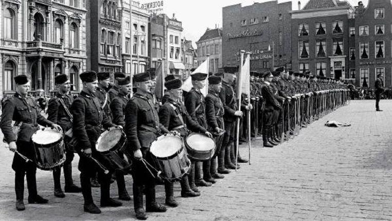Mei 1944. Leden van de Nederlandse Arbeids Dienst staan in het gelid voor het Scholtenhuis (links op de foto) op de Grote Markt in Groningen. Links- en rechtsonder beelden van de website. (ANP) Beeld
