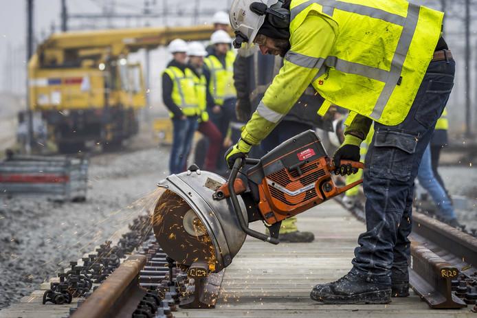 Werknemers werken aan een wissel op het spoor.