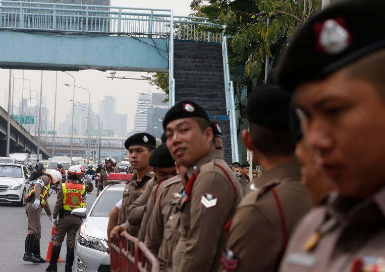 Thaise politie-agenten staan buiten het paleis in Bangkok waar de  bijeenkomst van 7 december over de volgende verkiezingen werd gehouden.  Beeld EPA