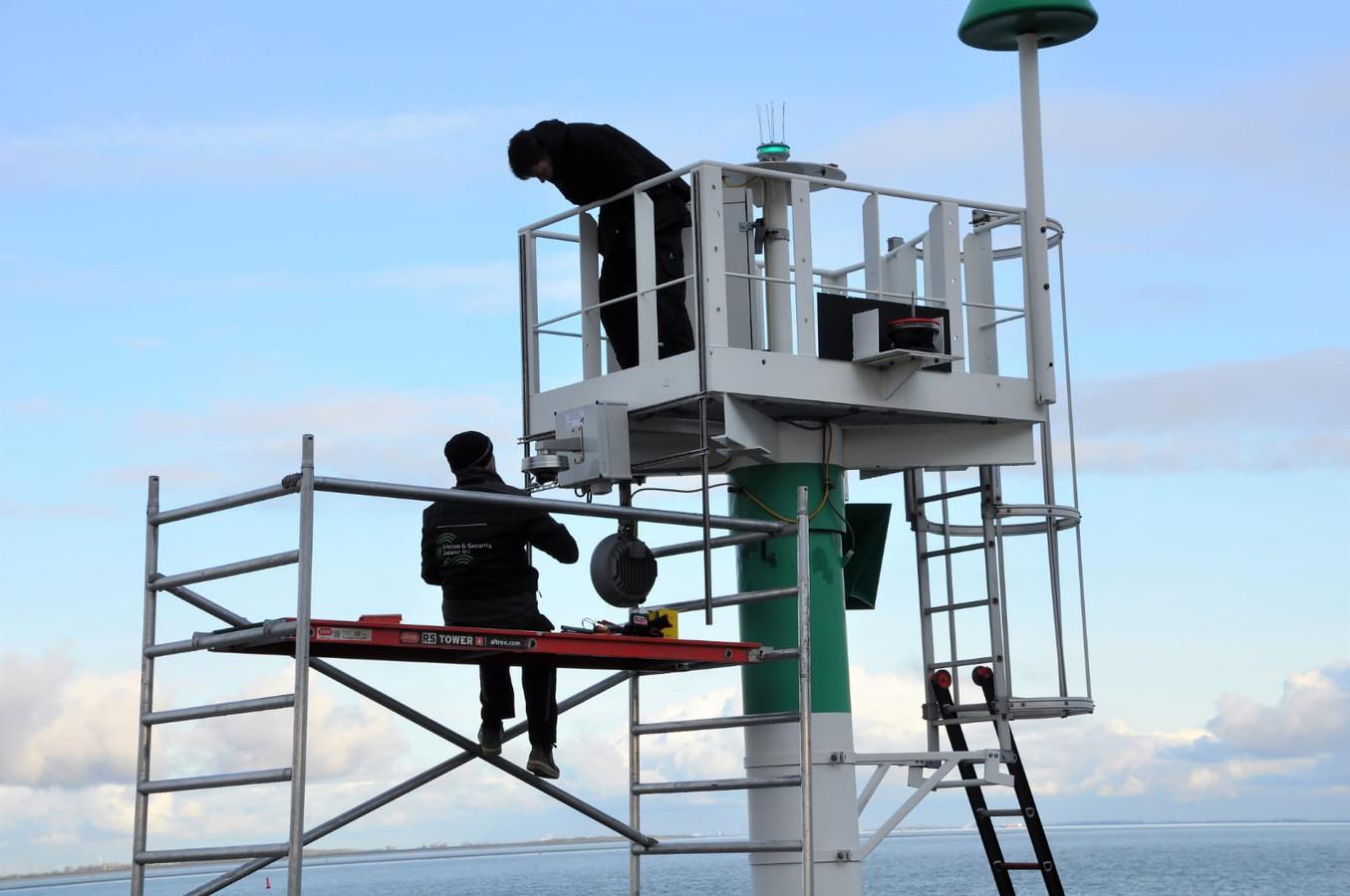 Beveiligingscamera wordt aangebracht op lichtopstand van Rijkswaterstaat bij de scheepsspotterplek in Terneuzen.