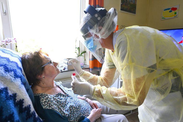 Een bewoner van een woon-zorgcentrum wordt getest op Covid-19-besmetting.  Beeld Photo News