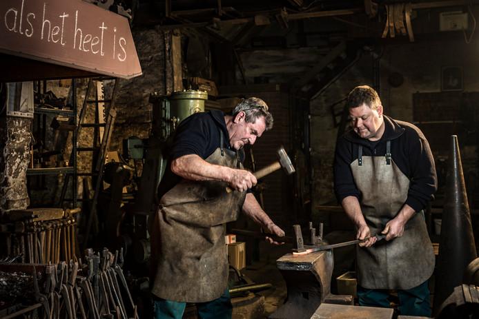 Erwin (l.) en zijn zoon Martin smeden het ijzer als het heet is.