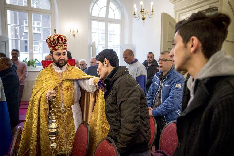 Hagop kust het kruis tijdens de dienst van de Armeens-apostolische Kerk. Links: priester Taron Tadevosyan. Beeld Rink Hof