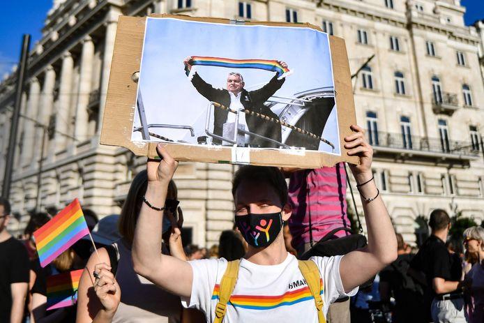 """Un participant tient une pancarte montrant le Premier ministre hongrois Viktor Orban tenant un foulard aux couleurs de l'arc-en-ciel, devant le bâtiment du Parlement à Budapest, le 14 juin 2021, lors d'une manifestation contre le projet de loi du gouvernement hongrois visant à interdire la """"promotion"""" de l'homosexualité et des changements de sexe."""