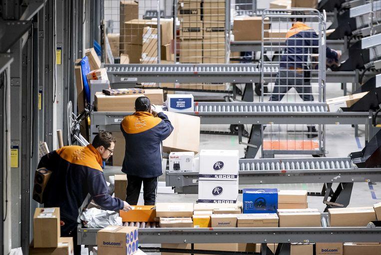 Medewerkers van post- en pakketbezorger PostNL sorteren pakketjes in het pakkettensorteercentrum.  Beeld ANP