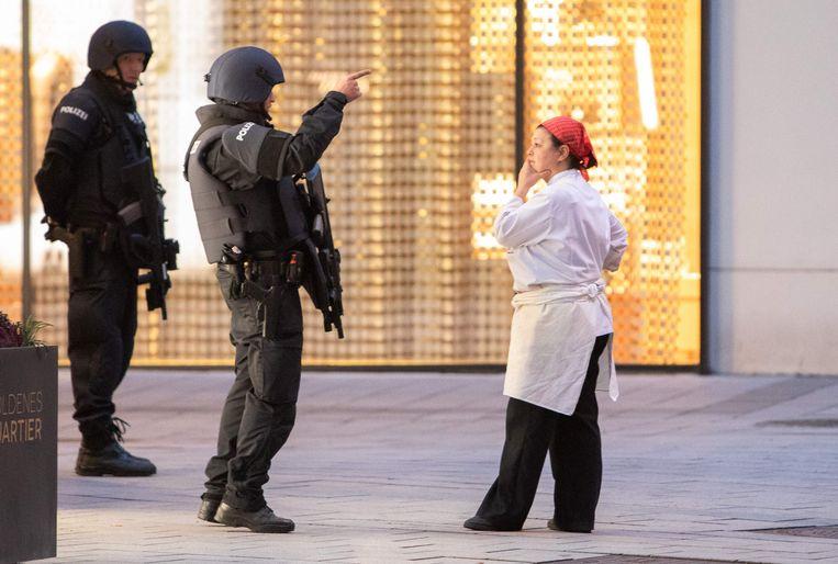Politieagenten praten met een vrouw bij Stephansplatz in centrum Wenen, na de schietpartij waarbij vier doden vielen Beeld AFP