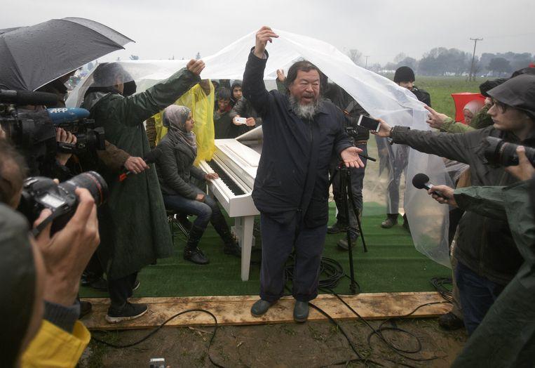 Ai Weiwei bij de pers, achter hem Nour Al Khzam die hij zaterdag liet piano spelen. Beeld AP