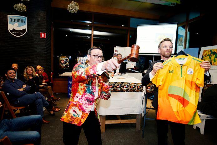 Veilingmeester Nielsson J. Kooijman en acteur Barry Atsma (r) veilen een vrijwilligersshirt van de Olympische Spelen in Rio. Het brengt 60 euro op.